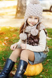 Adorable little girl is wearing winter clothes. Adorable happy little girl is wearing knitted hat sitting on pumpkin with autumn leaves on the nature Stock Photography