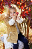 Adorable little girl is wearing winter clothes. Adorable happy little girl is wearing winter clothes is sitting on the chair with autumn leaves on the nature Stock Image