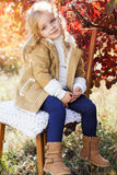 Adorable little girl is wearing winter clothes. Adorable happy little girl is wearing winter clothes sittting on the chair Royalty Free Stock Images