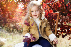 Adorable little girl is wearing winter clothes. Adorable happy smiling little girl is wearing winter clothes with autumn leaves on the nature Royalty Free Stock Photos