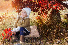 Adorable little girl is wearing winter clothes. Adorable little girl is wearing winter warm clothes with autumn leaves on the nature Stock Image