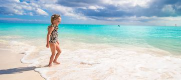 Adorable little girl on white beach during Stock Images
