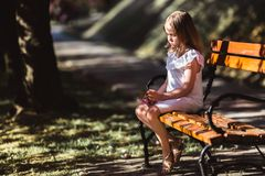 Adorable little girl in white dress in blooming pink garden on beautiful spring day. Adorable little girl in white dress sits on a bench in blooming pink garden royalty free stock photos