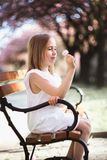 Adorable little girl in white dress in blooming pink garden on beautiful spring day. Adorable little girl in white dress sits on a bench in blooming pink garden stock photo