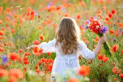 Adorable little girl with wild field flowers running thru meadow royalty free stock image