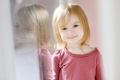 Adorable little girl by the window Royalty Free Stock Images