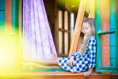Adorable little girl in the window of rural house Stock Photo
