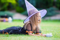 Adorable little girl in witch costume on Halloween Stock Photos