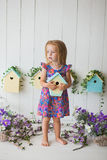 Adorable little girl on wooden background with birdhouse Stock Photography