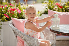 Adorable little girl 4 years old in a pink dress sitting in a white wicker chair and holding a white lantern for candle in the in stock photos