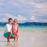 Adorable little girl and young dad on white sandy Stock Photo