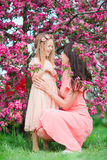 Adorable little girl with young mother in blooming cherry garden on beautiful spring day Royalty Free Stock Photo