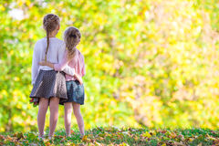 Adorable little girls with autumn leaves in the. Adorable little girls at beautiful autumn day outdoors Royalty Free Stock Image