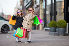 Adorable little girls with bags on shopping outdoors Royalty Free Stock Image