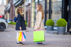 Adorable little girls with bags on shopping outdoors Royalty Free Stock Photo