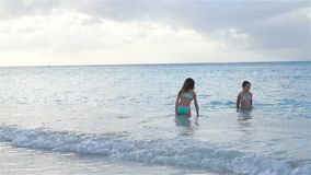 Happy little girls swimming in the sea during summer vacation. Adorable little girls during beach vacation having fun and swimming in the caribbean sea stock video