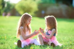 Adorable little girls on spring day outdoors sitting on the grass. Adorable little girls on beautiful spring day outdoors having fun together in the garden stock photography