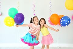 Adorable little girls at birthday party indoors. Adorable little girls with air balloons at birthday party indoors stock photography