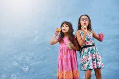 Adorable little girls blowing soap bubbles Stock Photos