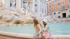 Adorable little girls on the edge of Fountain of Trevi in Rome. Happy kids enjoy their european vacation in Italy stock footage