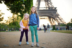 Adorable little girls enjoying themselves by the Eiffel tower in Paris Stock Photos