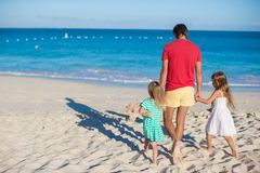 Adorable little girls and happy father on tropical white beach Royalty Free Stock Photo
