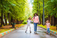 Adorable little girls with happy mom have fun on. Adorable little girls have fun on the scooter outdoor at autumn Royalty Free Stock Image