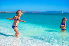 Adorable little girls have fun in shallow water at Stock Image