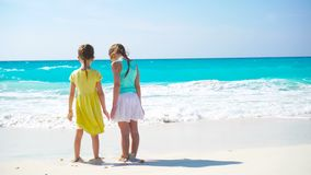 Adorable little girls have a lot of fun on the beach. Two beautiful kids running and splashing in shallow water. Adorable little sisters at beach during summer stock video