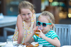 Adorable little girls having breakfast at outdoor Stock Photo