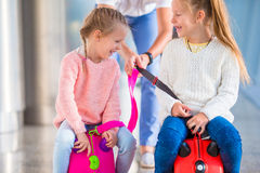 Adorable little girls having fun in airport sitting on suitcase waiting for boarding Royalty Free Stock Photos