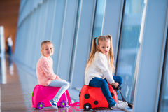 Adorable little girls having fun in airport waiting for boarding Royalty Free Stock Photos