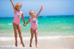 Adorable little girls having fun during beach. Adorable little sisters at beach during summer vacation Royalty Free Stock Image