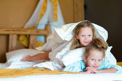 Adorable little girls having fun at bed inside Royalty Free Stock Image