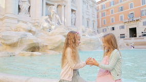 Adorable little girls having fun at the Fountain of Trevi in Rome. Happy kids enjoy their european vacation in Italy stock video