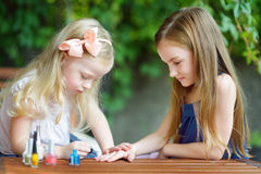 Adorable little girls having fun playing at home with colorful nail polish doing manicure and painting nails. To each other Royalty Free Stock Images