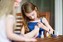 Adorable little girls having fun playing at home with colorful nail polish doing manicure and painting nails Royalty Free Stock Photo