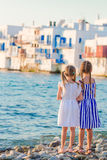 Adorable little girls at Little Venice the most popular tourist area on Mykonos island, Greece. Back view of beautiful Royalty Free Stock Photos
