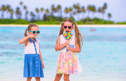 Adorable little girls with lollipop on tropical Stock Image
