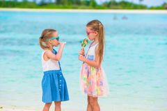 Adorable little girls with lollipop on tropical Stock Images