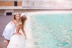 Adorable little girls near the Fountain of Trevi in Rome. Happy kids enjoy their european vacation in Italy Stock Photos