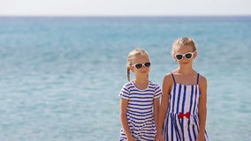 Adorable little girls ooking at camera together during beach vacation. Kids enjoy summer vacation in greek beach. Adorable little sisters at beach during summer stock video
