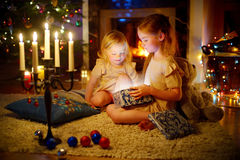 Adorable little girls opening a magical Christmas gift Stock Photos