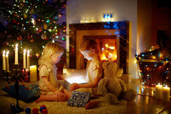 Adorable little girls opening a magical Christmas gift Stock Image
