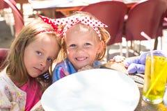 Adorable little girls in outdoor cafe Stock Photos