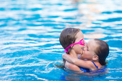 Adorable little girls in outdoor swimming pool on Stock Photo