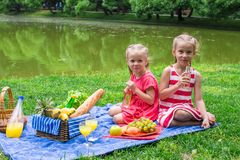 Adorable little girls picnicing in the park at Stock Image