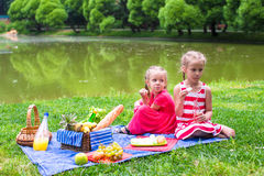 Adorable little girls picnicing in the park at Royalty Free Stock Photo