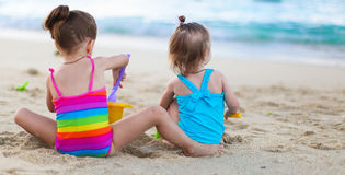 Adorable little girls playing with beach toys. Cute little girls playing with toys on beach vacation Royalty Free Stock Photography