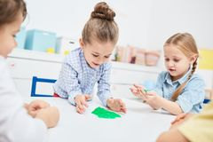 Funny toy. Adorable little girls playing with green funny slimes in kindergarten Stock Photos
